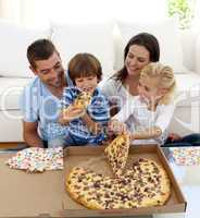 Young family eating pizza in living-room