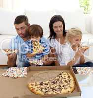 Family eating pizza in living-room