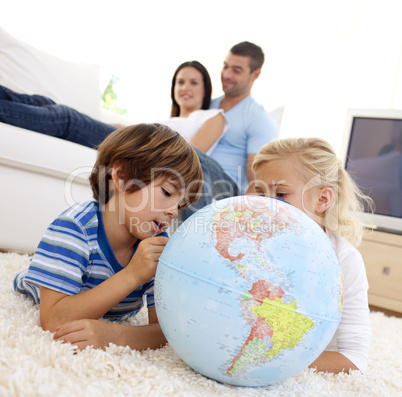 Children playing with a terrestrial globe in living-room