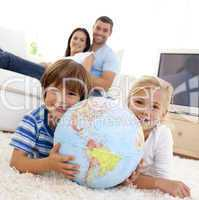 Children playing with a terrestrial globe at home