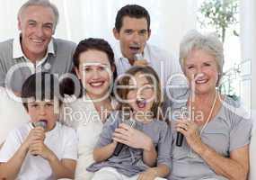 Happy family singing karaoke in living-room