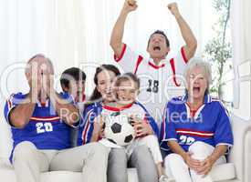 Family watching a football match in television