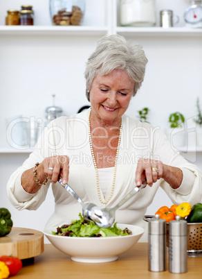 Happy senior woman cooking a salad