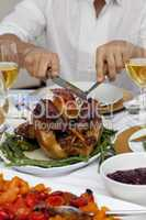 Close-up of a man cutting a turkey for Christmas dinner