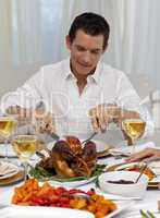 Attractive man eating turkey in Christmas dinner
