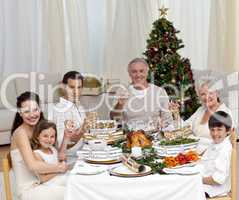 Family tusting with white wine in a Christmas dinner