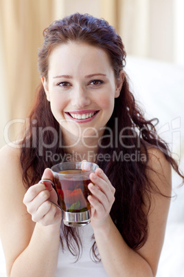 Smiling woman drinking a cup of tea in bedroom