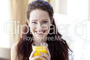 Girl drinking orange juice in bedroom