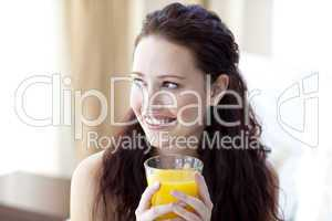 Woman drinking orange juice in bedroom