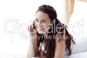 Beautiful woman lying in bed talking on phone