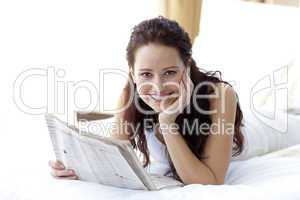 Smiling woman in bed reading a newspaper