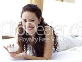 Smiling woman in bed taking pills
