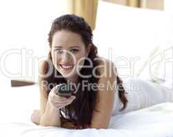 Beautiful woman in bedroom holding a remote control