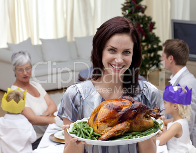Woman showing Christmas turkey for family dinner