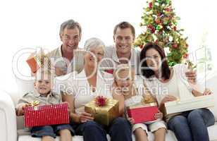 Family holding Christmas presents at home