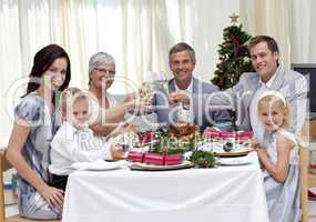 Family tusting in a Christmas dinner