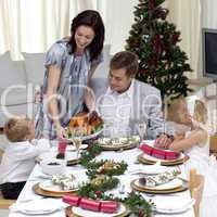 Parents and children in Christmas dinner with turkey