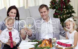 Parents toasting with wine in Christmas dinner