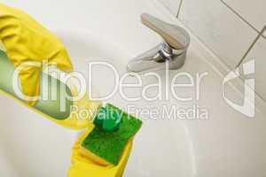 Hausfrau reinigt das Waschbecken mit Putzmittel