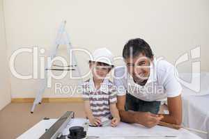 Smiling dad and little boy studying architecture