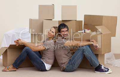 Smiling couple sitting on floor around boxes