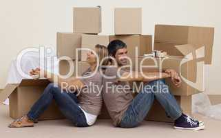Happy couple sitting on floor unpacking boxes