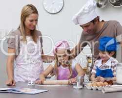 Parents helping children baking in the kitchen