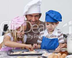 Father and daughter and son baking in the kitchen