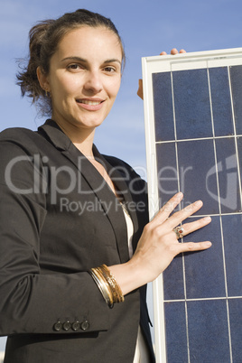 Frau hält ein Solarmodul