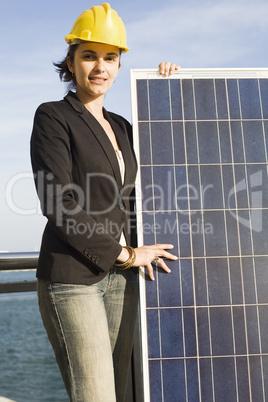 Eine Frau im gelben Helm hält einen Solarpanel