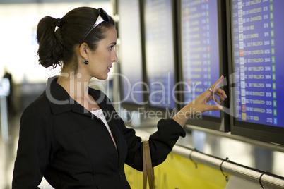 Hübsche Frau am Flughafen vor einem Informationsbildschirm