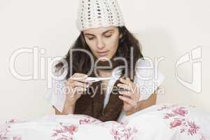 Junge Frau krank im Bett beim Themperatur messen
