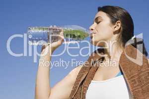 Junge Frau trinkt Wasser nach Sport vorm blauen Himmel