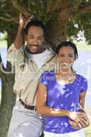 Happy African American Couple Holding Hands Under A Tree