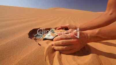 Geldscheine im Sand verstecken