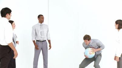 Geschäftsleute spielen Ball mit Weltkugel