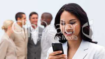 Smiling ethnic businesswoman sending a text
