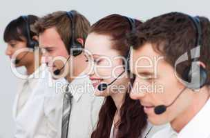 Beautiful woman working with other people in a call center