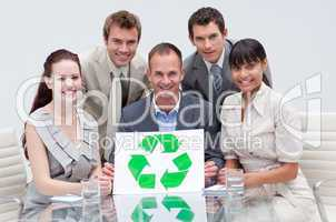 Smiling business team holding a recycling symbol. Ecological bus