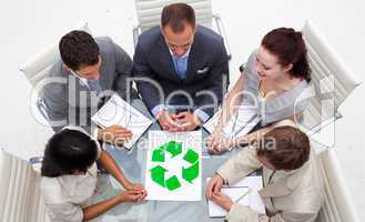 High angle of business team looking at a recycling symbol