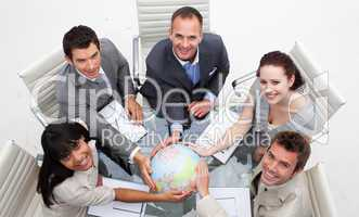 High angle of smiling business team holding the world
