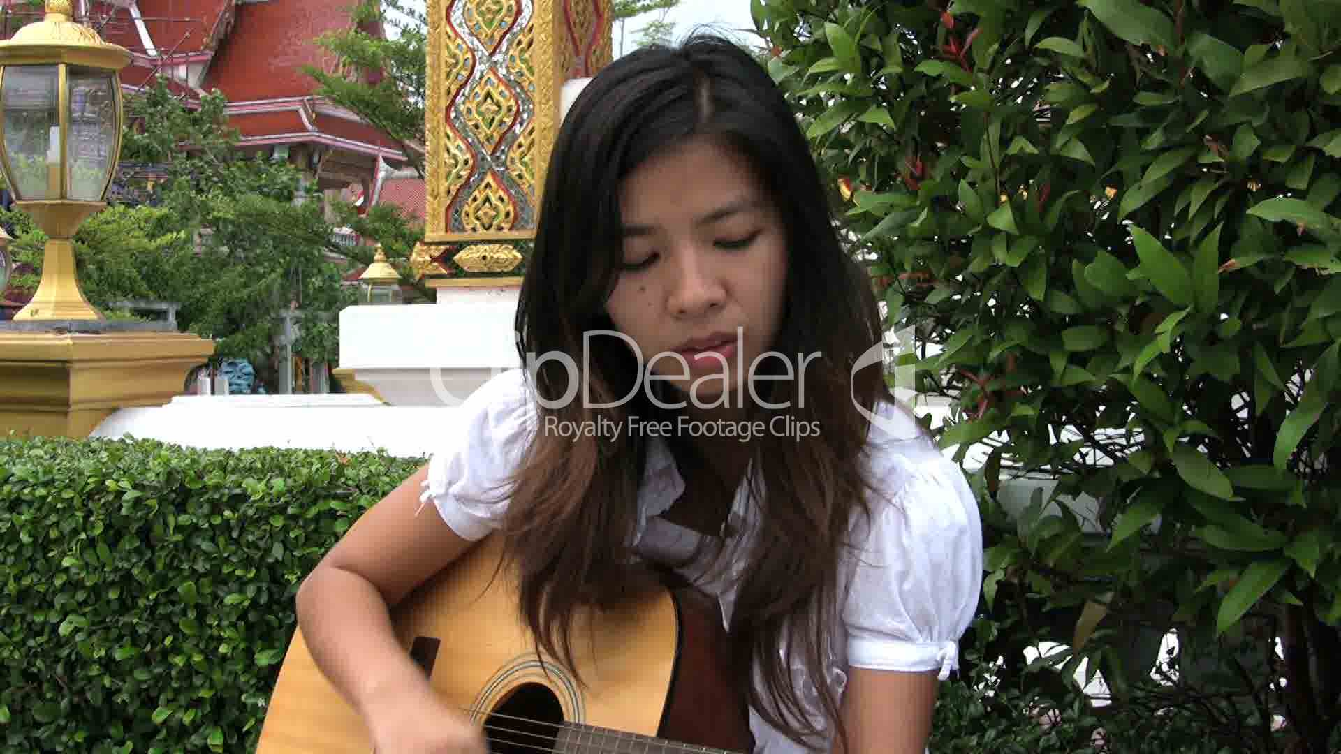 asian girl singing and playing guitar royalty free video