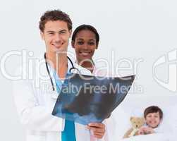 Smiling doctor and nurse examining an x-ray and a kid in bed