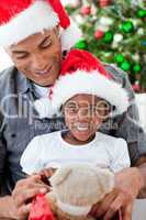 Happy little girl playing with a Christmas gift with her father