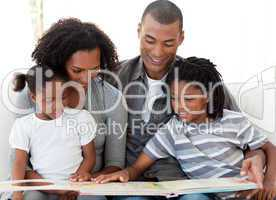 Afro-American family reading a book in the living-room