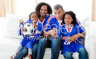 Afro-American family watching a football match at home