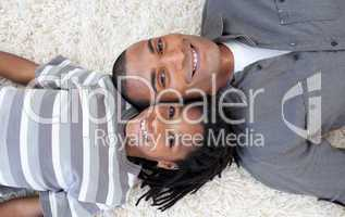 Smiling Afro-American father and son relaxing on the floor