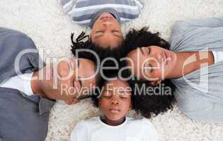 Afro-American family sleeping on floor with heads together
