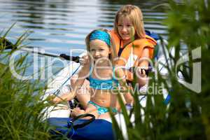 two young girls boating on the lake