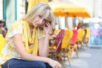 young blond woman is sitting in front of a sidewalk cafe